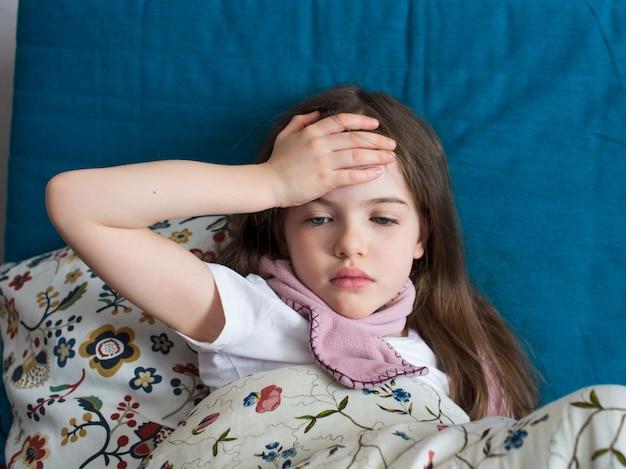 Een klein meisje heeft griep, ligt thuis onder een deken, haar hoofd doet pijn
