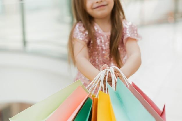 Een klein meisje heeft veelkleurige pasteltassen in haar handen. het concept van winkelen, winkelen in het winkelcentrum. detailopname