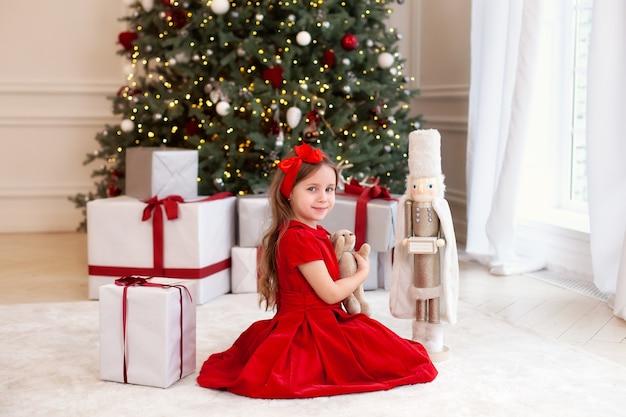 Een klein meisje houdt cadeau-teddybeer in de buurt van de kerstboom