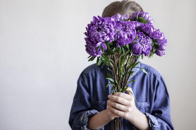Een klein meisje houdt een boeket blauwe chrysanten in haar handen, kopieer ruimte.