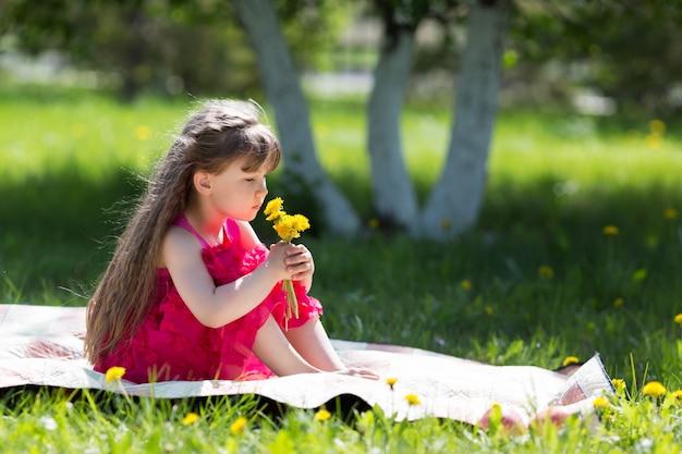 Een klein meisje houdt een boeket bloemen vast.