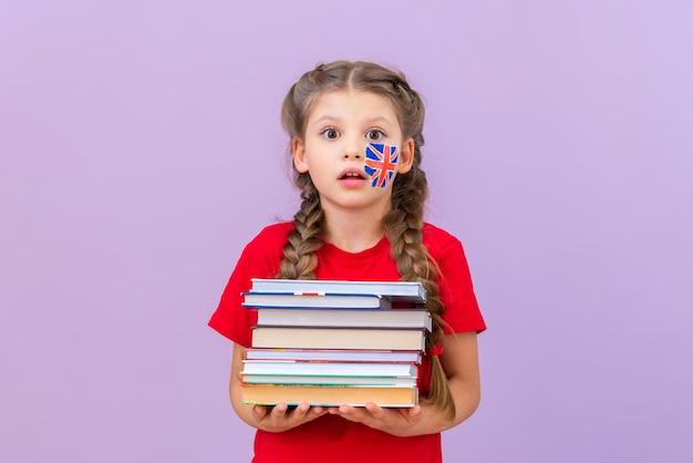 Een klein meisje houdt een grote stapel boeken over de engelse taal vast.