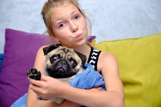 Een klein meisje houdt een mopshond vast gewikkeld in een handdoek