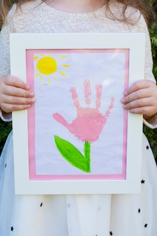 Een klein meisje houdt een tekening in een wit kader. palm bloemenprint