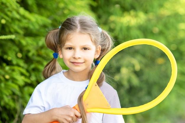 Een klein meisje houdt een tennisracket voor kinderen vast