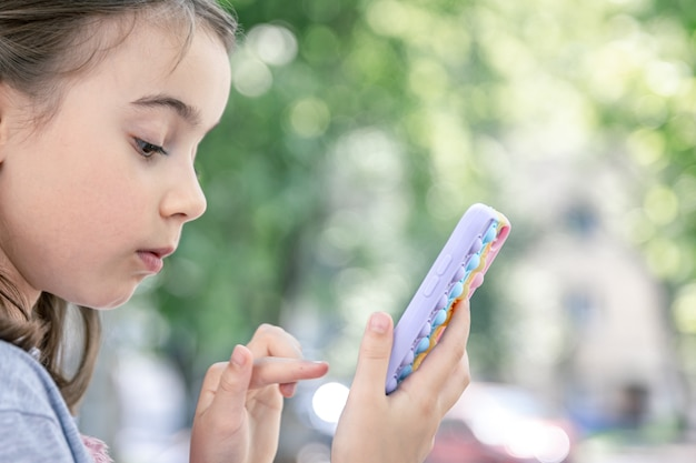 Een klein meisje houdt in haar hand een telefoon in een hoesje met puistjes erop, een trendy anti-stress speeltje.