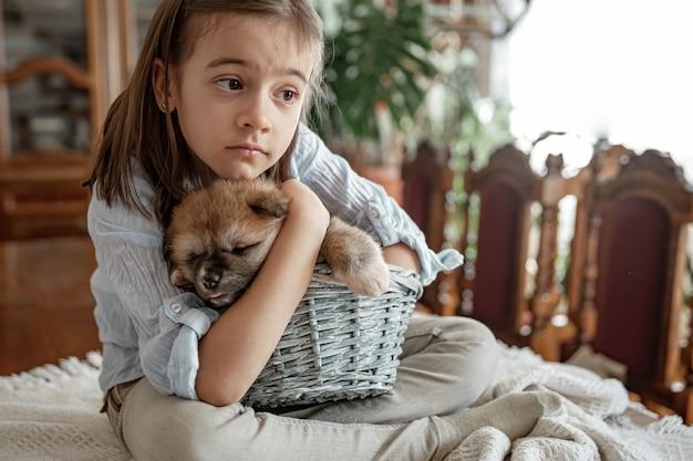 Een klein meisje houdt van en knuffelt haar kleine puppy.