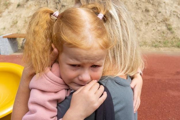 Een klein meisje huilt, begraven in de schouder van haar moeder. het concept van de emoties van kinderen.