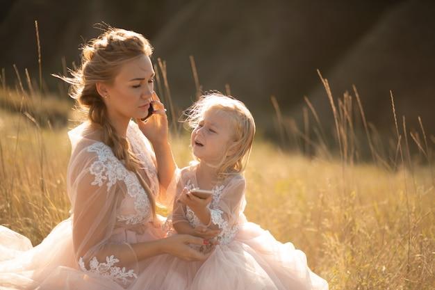 Een klein meisje huilt terwijl haar moeder aan het telefoneren is