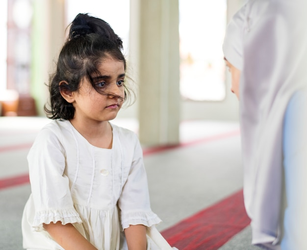 Een klein meisje in de moskee met haar moeder tijdens de ramadan
