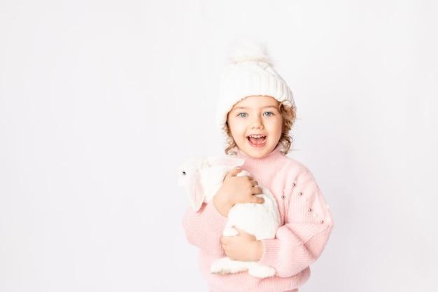 Een klein meisje in de winterkleren houdt een konijn op een witte achtergrond. nieuwjaars concept, ruimte voor tekst