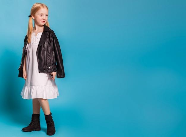 Een klein meisje in de witte jurk en zwarte schoenen