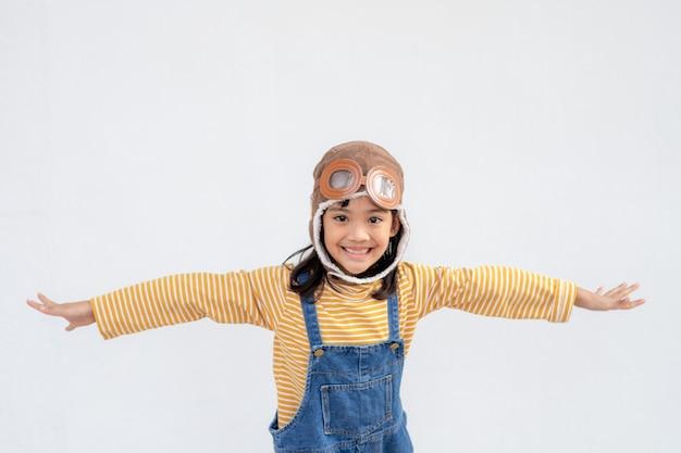 Een klein meisje in een astronautenkostuum speelt en droomt ervan ruimtevaarder te worden. op witte achtergrond