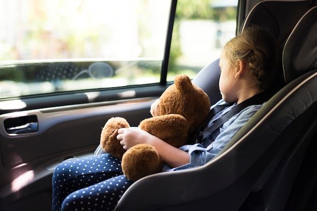 Een klein meisje in een autostoel