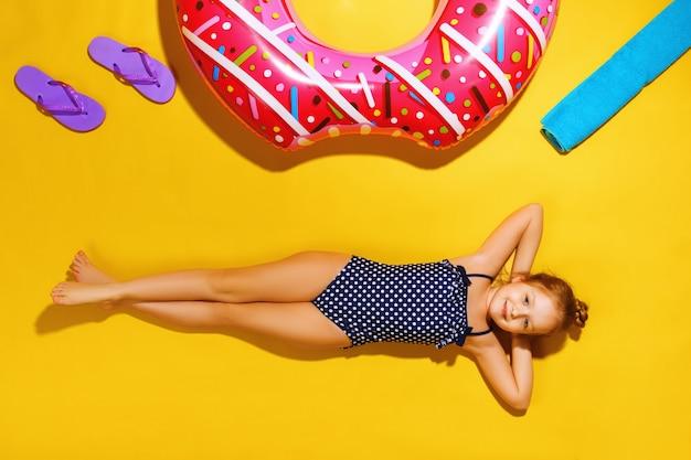 Een klein meisje in een badpak ligt met strandaccessoires om te zwemmen.