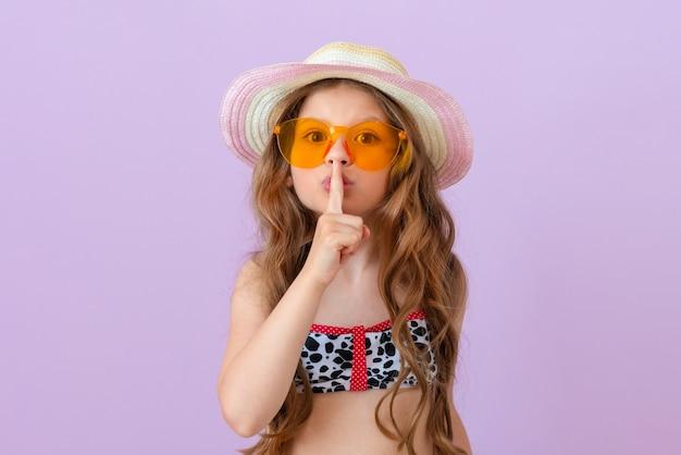 Een klein meisje in een badpak toont een vingergebaar, wees stil.