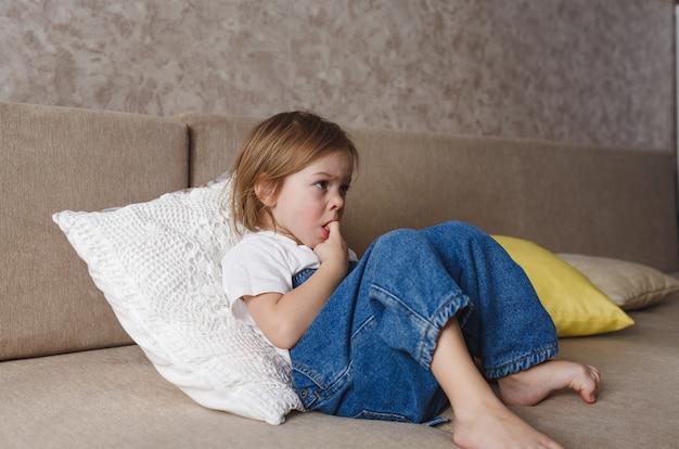 Een klein meisje in een blauwe denim jumpsuit zit op de bank en bijt op haar vingernagels