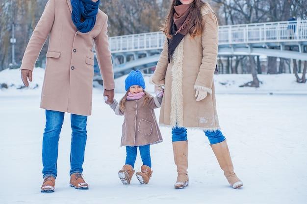 Een klein meisje in een blauwe hoed en een beige jas houdt haar ouders vast in de winter, achtergrond van een bevroren meer en een brug