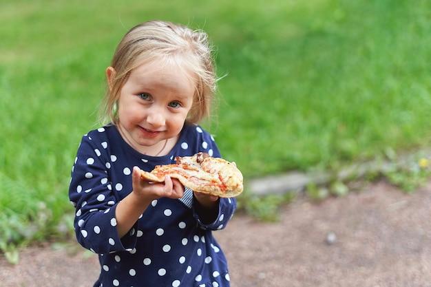 Een klein meisje in een blauwe jurk met witte stippen houdt de camera een groot stuk pizza voor