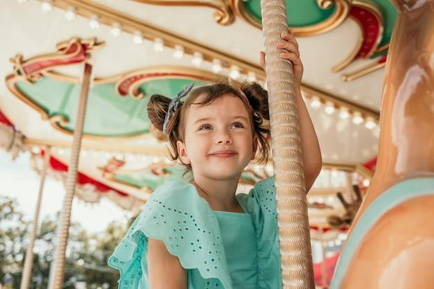 Een klein meisje in een blauwe jurk rijdt op een attractie in een pretpark