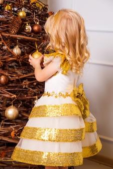 Een klein meisje in een chique wit-gouden jurk staat met haar rug naar de camera en versiert de kerstboom