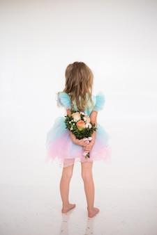 Een klein meisje in een feestelijke jurk met een tutu-rok staat met haar rug en houdt een boeket verse bloemen vast op een witte achtergrond met een plek voor tekst