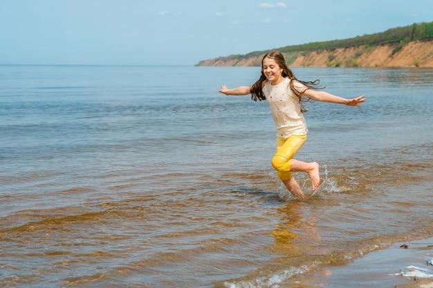 Een klein meisje in een felgele broek rent in het water en dartelt op het strand
