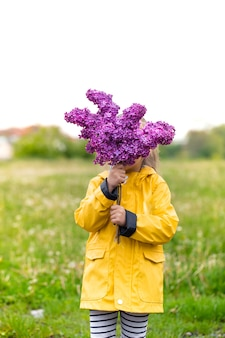 Een klein meisje in een geel jasje bedekt haar gezicht met een boeket seringen. creatief