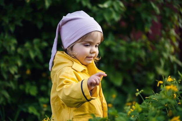 Een klein meisje in een geel jasje staat bij gele bloemen
