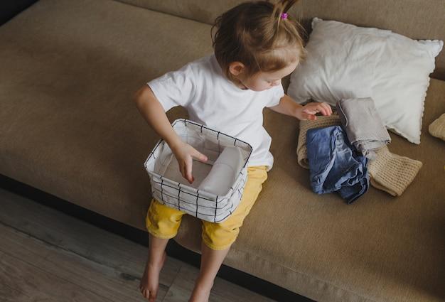 Een klein meisje in een gele broek en een wit t-shirt zit op de bank en vouwt haar kleren netjes op in een opbergdoos. mama's assistent.