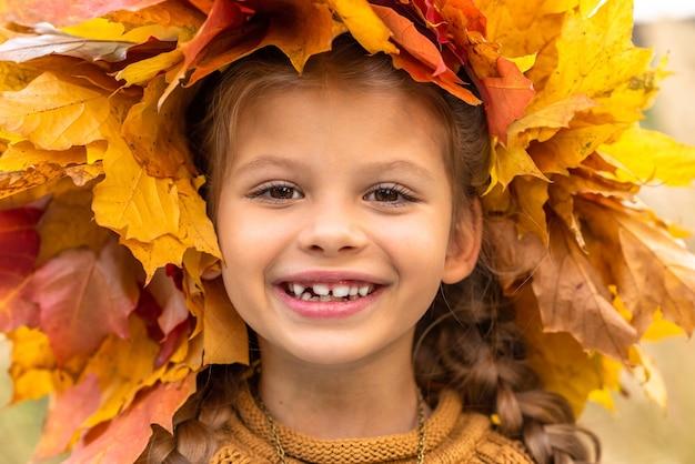 Een klein meisje in een herfsttrui en een esdoornkrans.