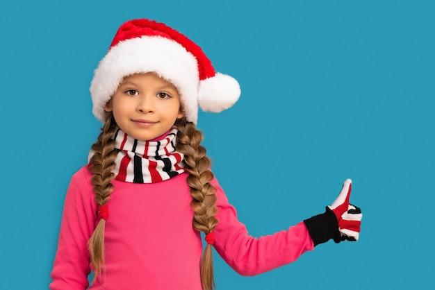 Een klein meisje in een kerstmuts steekt een duim op