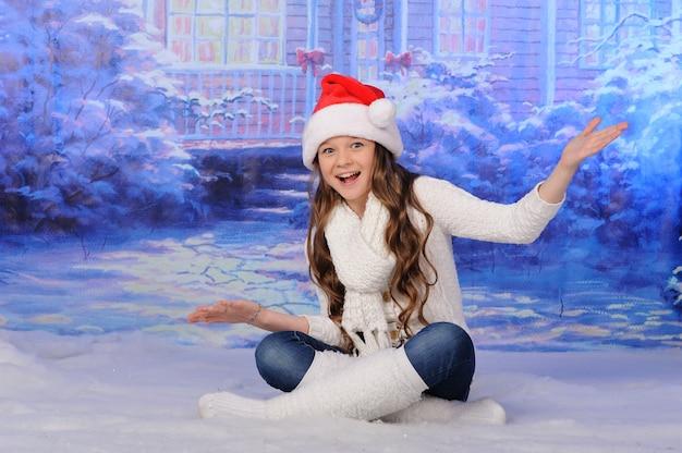 Een klein meisje in een kerstmuts zit in de sneeuw.