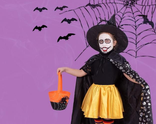 Een klein meisje in een kostuum en enge make-up met een snoepmand