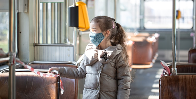 Een klein meisje in een leeg openbaar vervoer tijdens het pandemische coronavirus.