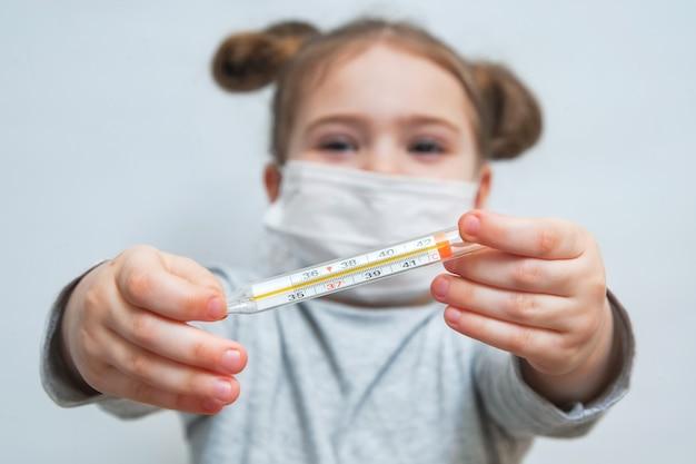 Een klein meisje in een medisch masker toont de thermometer. medisch concept van epidemiologische periode, luchtwegaandoeningen en hoge temperaturen. coronavirus epidemische bescherming