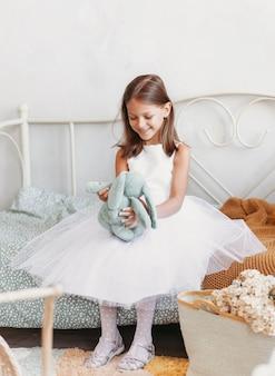 Een klein meisje in een mooie jurk speelt op het bed met een knuffel.