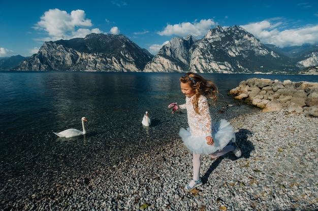 Een klein meisje in een nette witte jurk loopt langs de oever van het gardameer, een meisje wordt gefotografeerd tegen de achtergrond van een berg en een meer in italië, torbole.
