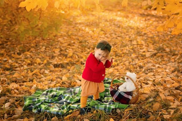 Een klein meisje in een rode trui knuffelt een liefdevol speeltje en knuffelt het haar