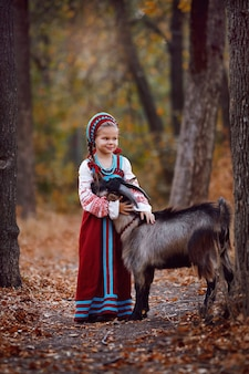 Een klein meisje in een rode zomerjurk staat naast een zwarte jonge geit in het herfstbos