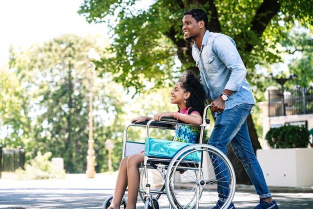 Een klein meisje in een rolstoel die geniet van en plezier heeft met haar vader terwijl ze samen buiten wandelt