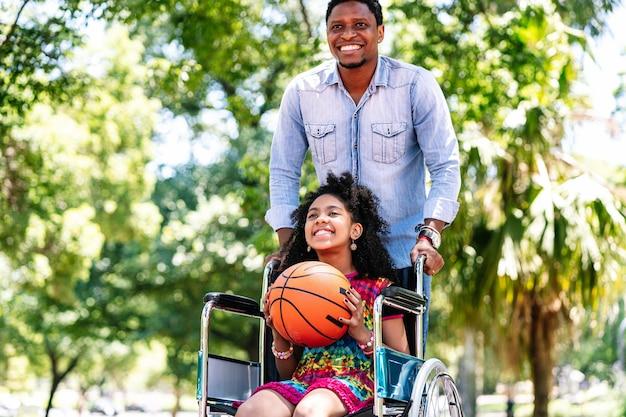 Een klein meisje in een rolstoel die plezier heeft met haar vader terwijl ze samen basketbal speelt in het park.
