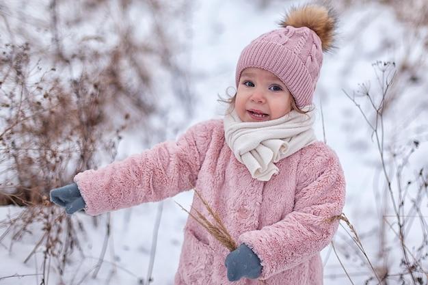 Een klein meisje in een roze bontjas heeft plezier, buiten spelen, omgeven door sneeuw. wintertijd, het concept van gezonde kinderactiviteiten