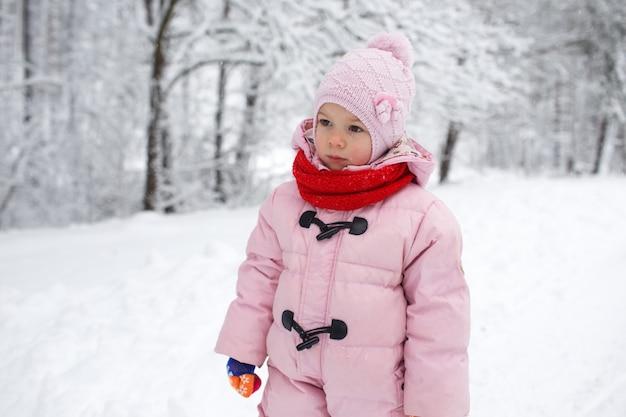 Een klein meisje in een roze jasje staat in een besneeuwd bos. kinderspellen in het besneeuwde bos. familie wintervakantie met een kind