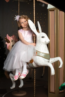 Een klein meisje in een roze jurk en een kroon op een carrousel met een witte haas.
