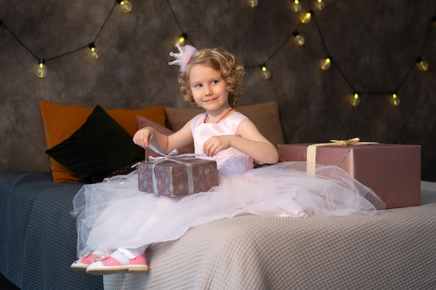 Een klein meisje in een roze jurk en een kroon op het bed met cadeautjes.