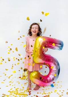 Een klein meisje in een roze jurk houdt een veelkleurig nummer vijf vast op een witte achtergrond met gouden confetti