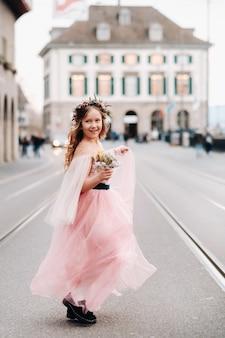 Een klein meisje in een roze prinses jurk met een boeket in haar handen loopt door de oude stad zürich. portret van een meisje in een roze jurk op een straat in de stad in zwitserland.