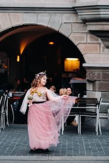 Een klein meisje in een roze prinsessenjurk met een boeket in haar handen loopt door de oude stad zürich