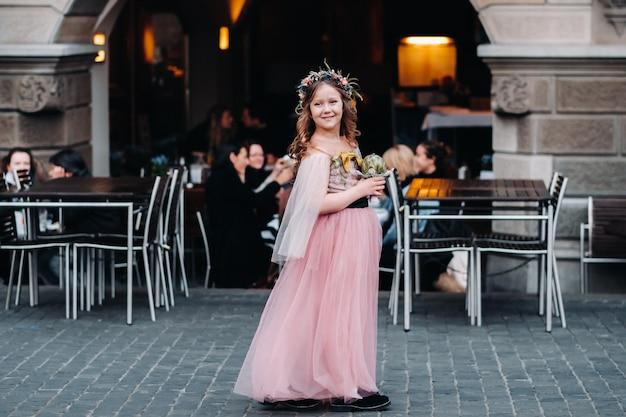 Een klein meisje in een roze prinsessenjurk met een boeket in haar handen loopt door de oude stad zürich.